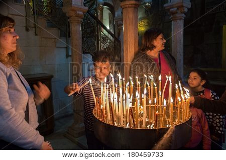 JERUSALEM ISRAEL - MARCH 31 2017: Pilgrims family lights a candle in the Holy Sepulchre on Mount Calvary Jerusalem Israel