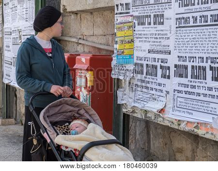 Orthodox Jewish Woman With Child Read Street Poster In Jewish Quarter. Jerusalem. Israel