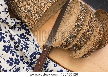 Whole Wheat Sliced Bread Closeup , On Wooden Surface With Floral Kitchen Towel And Knife