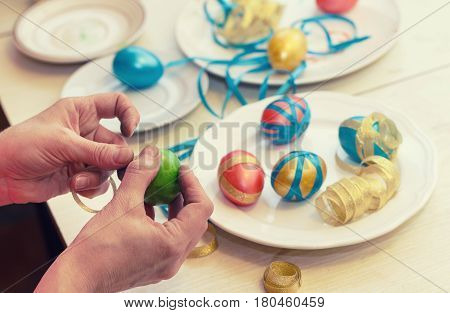 Women's hands are decorated with Easter eggs.