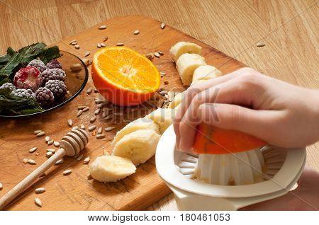 Cooking,hand Squeezes Orange Juice, Banana,frozen Strawberries Blackberries And Seeds Vivid Smoothie