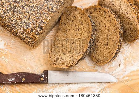 Whole Wheat Sliced Bread With Knife, On Wooden Surface With Flour.