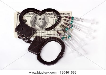 handcuffs ,dollars and used syringes, white isolated closeup