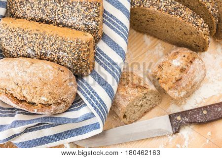 Whole Wheat Bread Buns And Slices, On Wooden Surface With Flour.