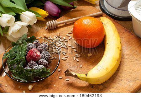 banana orangefrozen strawberries blackberries and seeds vivid smoothie ingredients and blender juicer tulips on the background on wooden