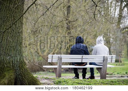 Two young men with hoods on a bench from behind in bad weather in the park couple homosexuals refugees homeless or just friends copy space