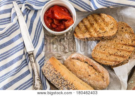 Whole Wheat Bread Buns And Grilled  Bread Slices, With Roasted Red Peppers In Bowl And Knife.