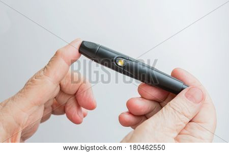 A woman holds a lanset and pierces her finger to check the blood sugar level.