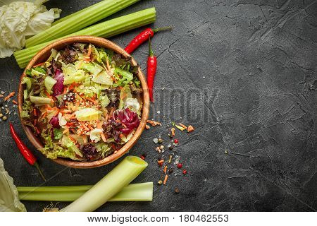 Wooden bowl with mix of salad freeze lollo rosso radicchio romano and iceberg with carrots on black background. Top view with place for text