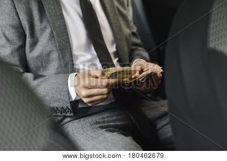 a young caucasian man in an elegant gray suit counts euro bills sitting in the back seat of a car