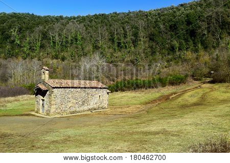 a view of the old small church dedicated to Saint Margaret in the crater of the Santa Margarida Volcano in the Garrotxa Volcanic Zone Natural Park, in Olot, Spain