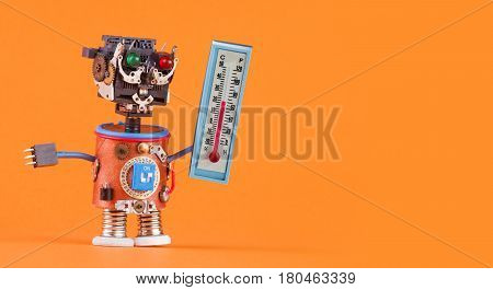 Weathermen robot with thermometer displaying comfort room temperature 21 degree celsius. Weather forecasting concept photo. Funny head robotic toy character on orange background, copy space.