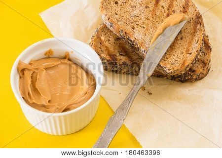 Spreading Peanut Butter On Whole Wheat Grilled  Bread Slice