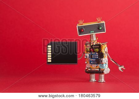 Portable storage device memory card concept. Abstract robot system administrator with electronic computing chip circuit on red background. Macro view copy space.
