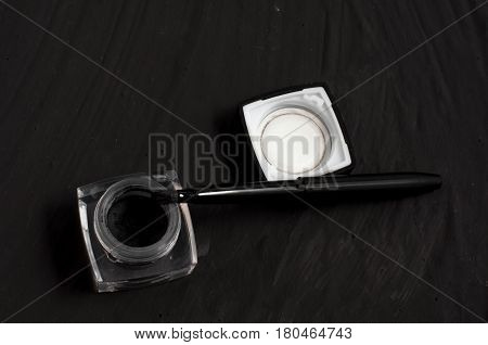 Eyeliner and brush on black background. Makeup set background.