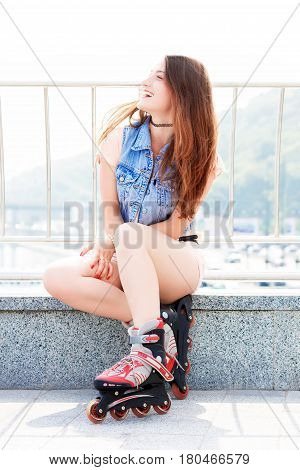 Girl wearing roller skates sitting on the street and smiling