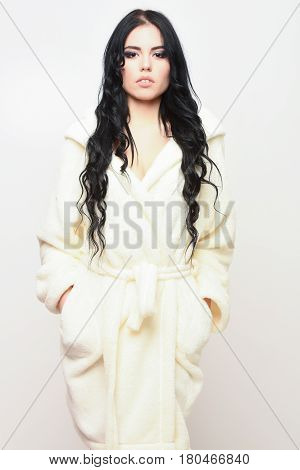 pretty serious cute sexy girl or beautiful woman with fashion makeup and curly long hair posing in beige velour bathrobe isolated on white background