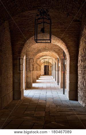 Barcelona Spain - September 25 2015: View of cloister inside Barcelona Montjuic castle. Copy space on black ceiling.