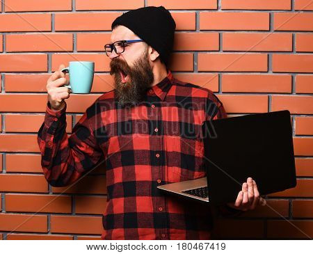 Bearded man long beard. Brutal caucasian shouting unshaven hipster holding laptop with mag or cup in red black checkered shirt with hat and glasses on brown brick wall studio background