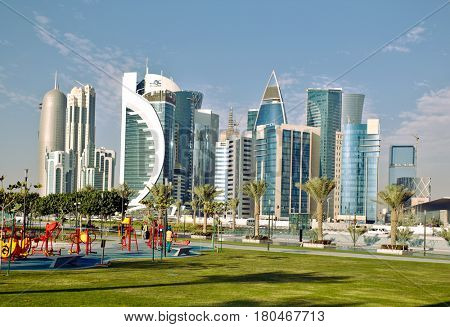 DOHA, QATAR - FEBRUARY 17, 2016: The high-rise district of Doha, seen from the recently completed Hotel Park, with a children's playground in the foreground.