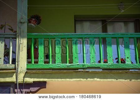 Photo of a green railing with wood, several colours and sunlight