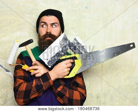 bearded man long beard brutal caucasian hipster with moustache holding various building tools: saw hammer roller paint with surprised face on studio wall background