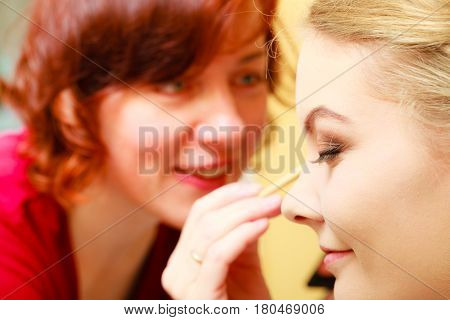 Visage concept. Close up woman getting make up on eyebrows. Applying eyeshadow on eyebrow with brush by woman. Eyes closed.