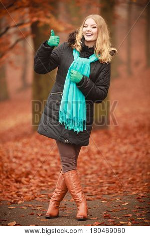 Outdoor nature leisure foliage vegetation concept. Smiling lady walking through park. Young blonde taking a walk in autumnal woodland wearing blue scarf.