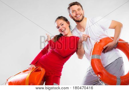 Accident prevention and water rescue. Young man and woman lifeguard couple on duty holding ring buoy float lifesaver equipment having fun on gray