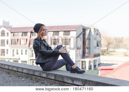 Young blond woman in black relaxes on the edge of roof in the city center