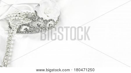 Bridal wedding decorations soft white bride background silver crown and pearls on satin with space for text