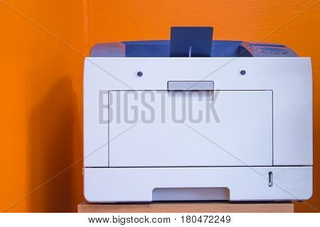Modern digital printer with eyes isolated on orange background