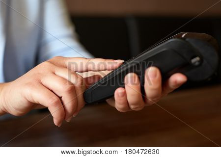 Female Hand Entering Pin Number Using Payment Terminal