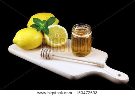 A bunch of lemons and a honey jar on cutting board