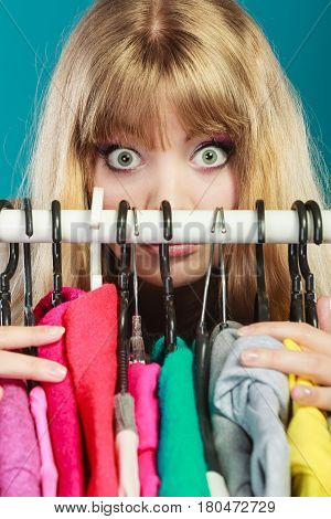Pretty woman hiding behind clothing in wardrobe. Young undecided shopper girl making big eyes. Shopaholic concept.