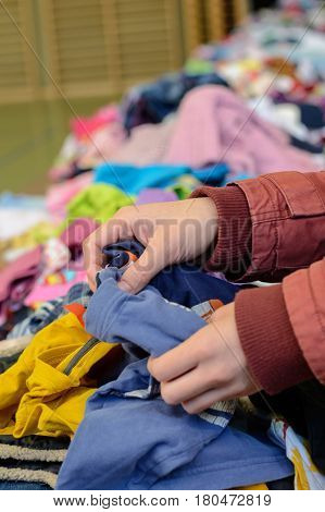 Person searches in clothes selection at a children 's dress basement - detail