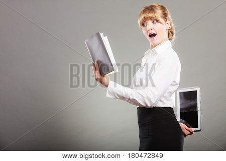 Woman learning with book holding ebook reader behind back. Choice between modern educational technology and traditional way method. Girl hold digital tablet pc and textbook. Contemporary education.