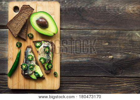 Open faced sandwich with avocado sardine and jalapeno on dark rye bread on rustic wooden background. Healthy snack. Top view.