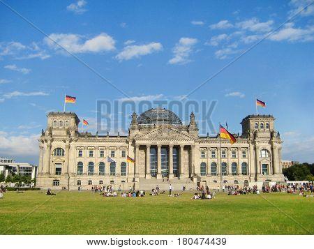 Reichstag building, headquarter of German Parliament (Deutscher Bundestag) in Berlin, Germany at Konigsplatz, with german flags raised. Summer colorful scene with green grass blue sky empty background