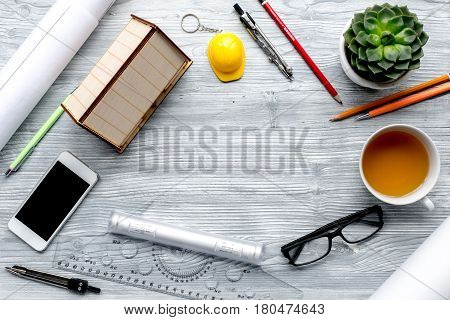 profession concept with architect desk and constructor tools and phone on light wooden background top view mockup