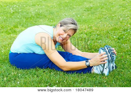 Fitness and healthy lifestyle. Senior woman doing exercise in the park.