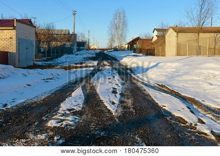Spring slush in a village street with snow