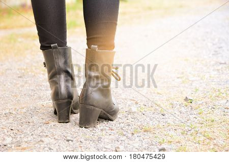 A woman legs wearing black boots with high heel.