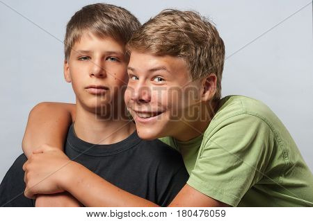 Two Boys, One Is Hugging The Other Smiling The Other Face Is Annoyed