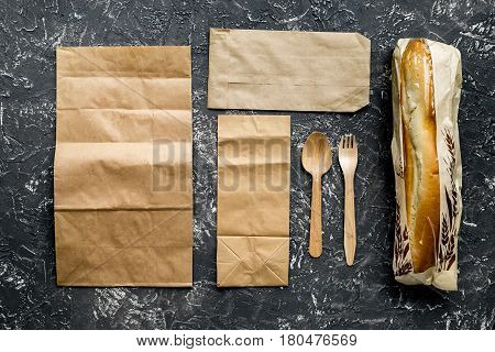 delivery service set with paper bags and sandwich on gray desk background top view