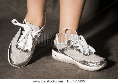 Female legs in silver fashionable sport shoes on gray background.