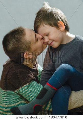 Young mother hugging her son. Kisses him on the cheek. Baby full of love and tenderness.