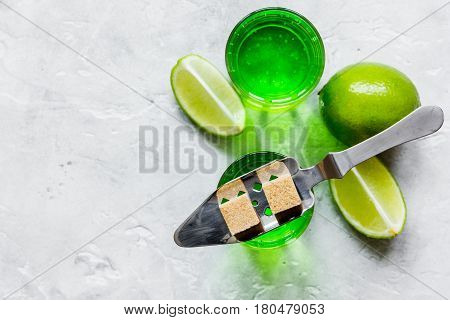 green shots with sugar cubes and fresh lime slices on stone bar table background top view mock-up