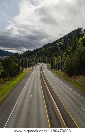 Aerial view of a four lane interstate highway that cuts through a mountainous forrested area in central Oregon.