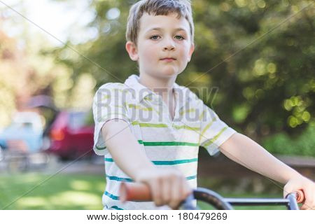 Young boy sitting on a bicycle with a serious look on his face. Green home back yard setting.